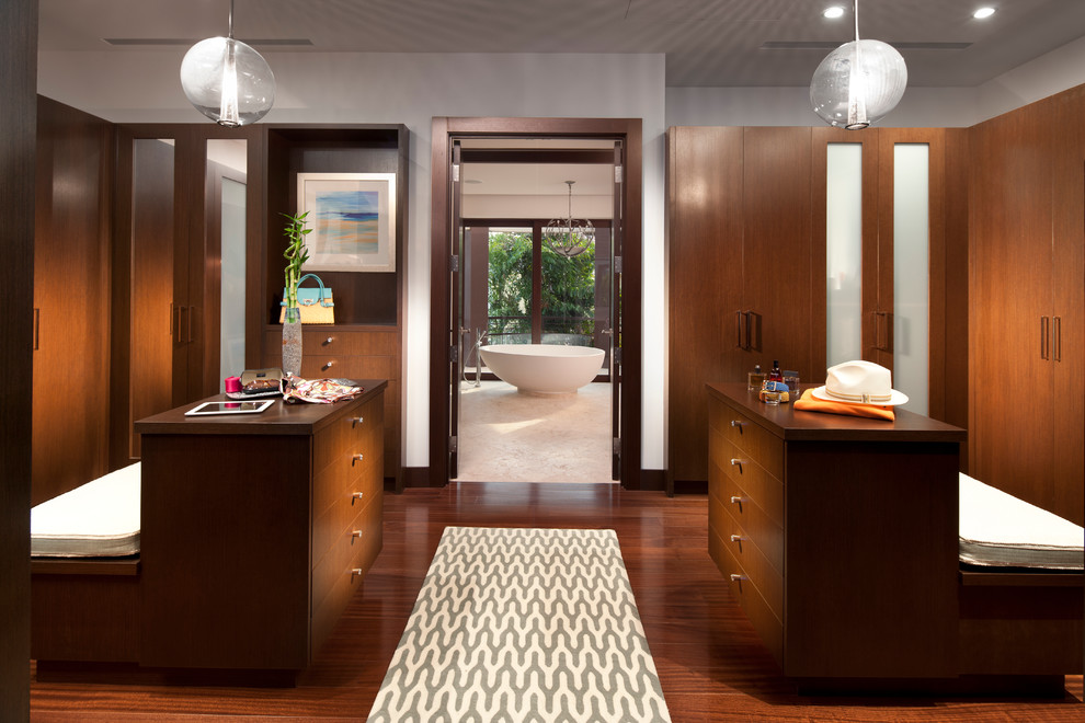 A contemporary master closet design for HIM and for HER.