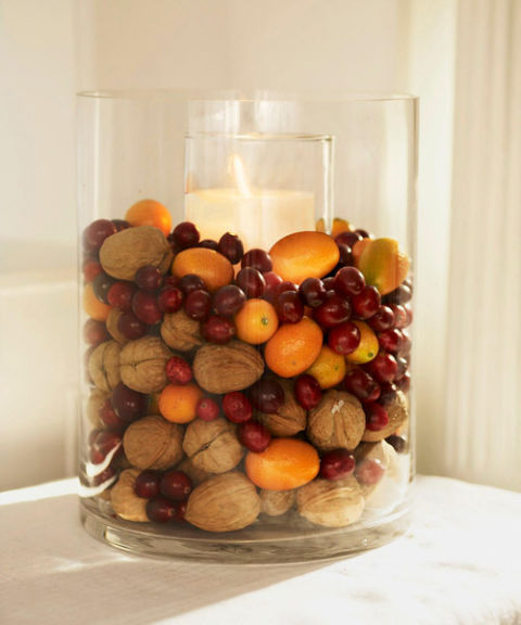 Heaped with walnuts, cranberries and kumquats, a cylinder vase displays festive flavors. Place a tall pillar candle and holder inside the vase; surround with fruits and nuts. What you'll need:glass vase ($9,amazon.com), walnuts($17,amazon.com)
