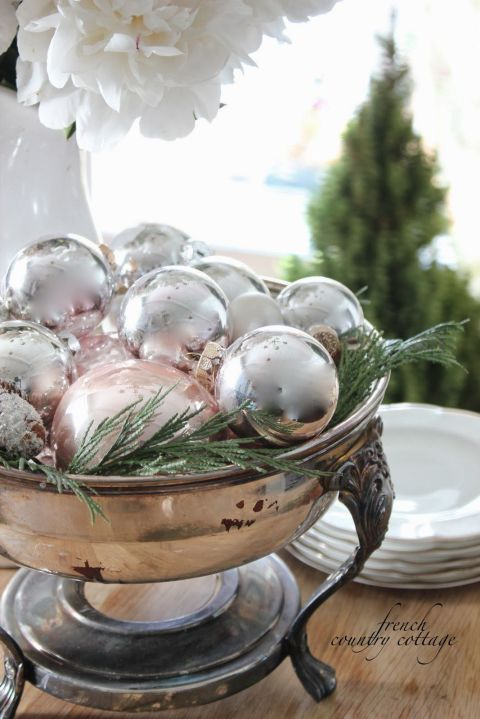 Shiny ball ornaments don't just look good on trees — they actually make for a lovely holiday centerpiece, tucked neatly into a bowl full of greens. See more at French Country Cottage » What you'll need:silver ornaments($9,amazon.com), bowl($20,amazon.com)