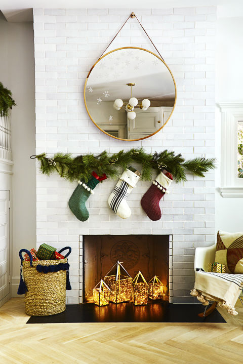 Use a washable-paint marker to add fluttery flakes to a mirror. Festive stockings — attached to a faux garland — and a tassel basket hold plenty of goodies. What you'll need: paint pen ($9, amazon.com), pine garland ($20, target.com), stockings ($13 each, target.com), basket ($98, crateandbarrel.com)